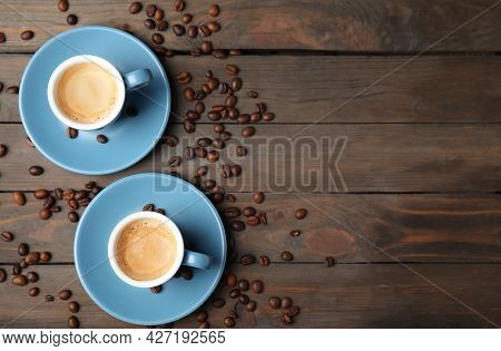 Cups Of Tasty Espresso And Scattered Coffee Beans On Wooden Table, Flat Lay. Space For Text