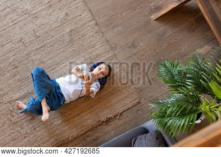 Ten-year-old Girl Listening To Music And Relaxing While Lying On The Floor At Home. She Listens To M