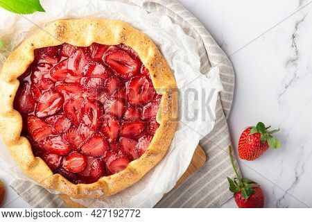Fresh Homemade Galette With Strawberries On White Marble Background. Top View. Close-up.