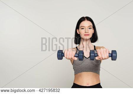 Sportswoman With Vitiligo Exercising With Blurred Dumbbells Isolated On Grey