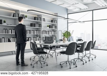 Businessman Standing In Modern Meeting Room Interior With Furniture, Bookcase And City View. Corpora