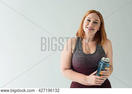 Smiling Plus Size Sportswoman Holding Sports Bottle Isolated On Grey