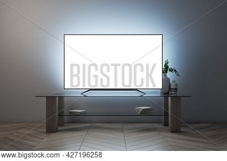 Illuminated White Tv Screen With Furniture On Concrete Wall Background. Television Concept. Mock Up,