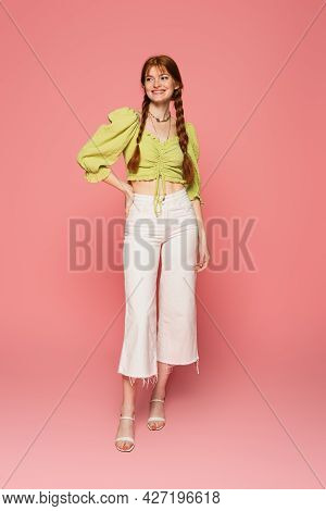 Cheerful Woman With Freckles Standing On Pink Background