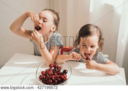 Happy Children Eat Summer Berries. Delicious Bright Juicy Berries. Children In Striped T-shirts Eat.