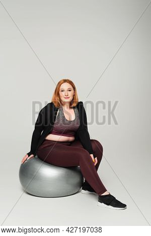 Plus Size Sportswoman Sitting On Fitness Ball And Looking At Camera On Grey Background