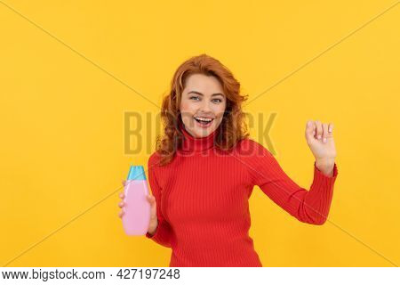 Happy Dancing Redhead Woman Curly Dyed Hair Presenting Body Care Product Of Shampoo, Hair Treatment