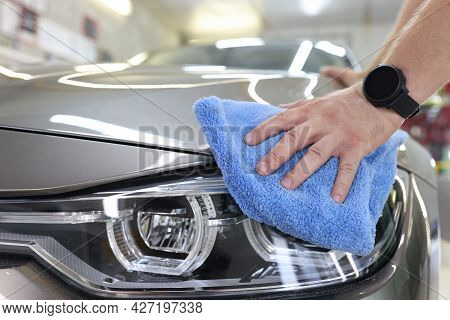 Man Who Decorates Cars Holds Microfiber In Hand And Polishes Car