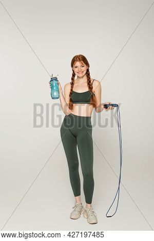Cheerful Sportswoman With Freckles Holding Jump Rope And Sports Bottle On Grey Background
