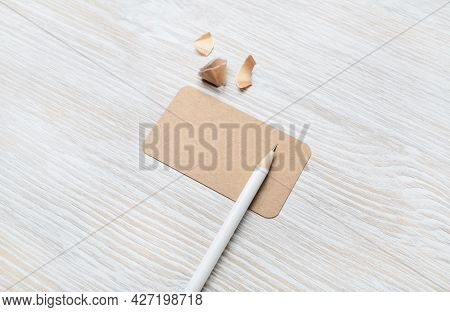 Blank Kraft Business Card And Pencil On Light Wood Table Background. Template For Graphic Designers