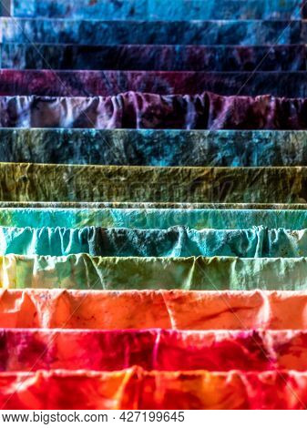 Closeup of various colors hand-dyed wet cotton fabrics drying on a drier