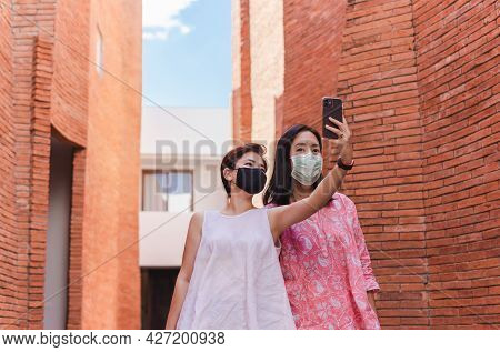 Two Woman Friends With Protective Masks Taking Selfie Using Cell Phone