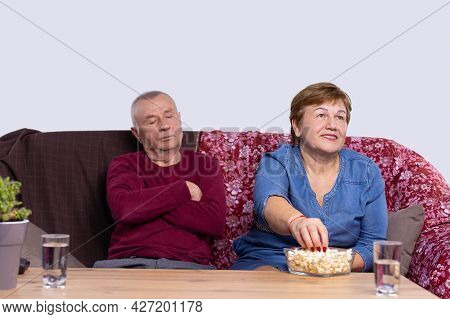 An Old Man Sleeping On A Couch, His Old Wife Eating Popcorn And Watching Tv-set With Two Glasses Of