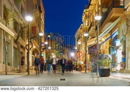 Heraklion, Crete, Greece - April 26, 2018: 25th August street in Heraklion city at night with walking people. People are blurred in motion
