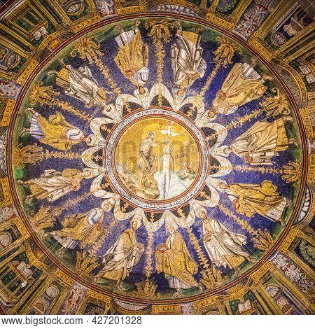 Ravenna, Italy - October 14, 2016: Mosaic cupola in the Neoniano Baptistery in Ravenna - John the Baptist baptizing Jesus and the Apostles round, cerca 5th century