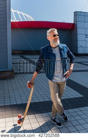 Full Length Of Happy Middle Aged Man In Sunglasses Holding Longboard And Standing With Crossed Legs