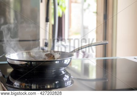 A Portrait Of A Frying Pan Baking Some Bacon On A Induction Furnace, Which Has The Pans Reflection I