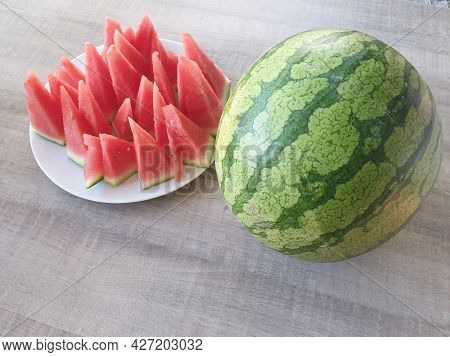 A Portrait Of An Uncut Green, Big And Round Watermelon Next To A White Plate Full Of Red Pointy Slic