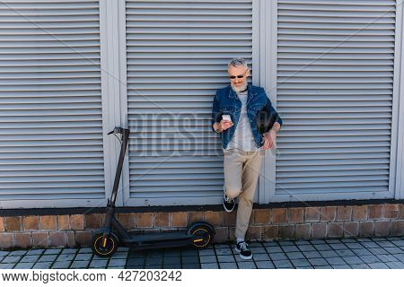 Full Length Of Happy And Mature Man In Sunglasses Using Smartphone Near E-scooter