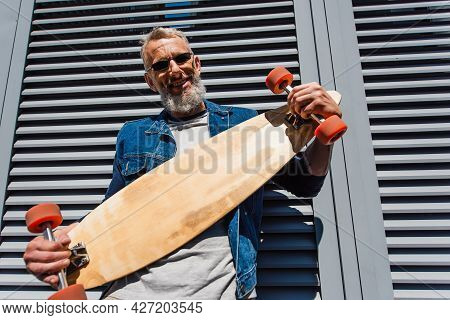 Pleased Middle Aged Man In Sunglasses Holding Longboard