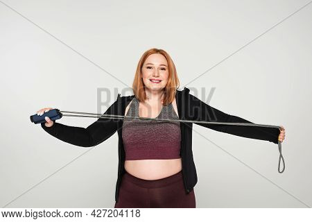 Young Body Positive Sportswoman Holding Mump Rope Isolated On Grey