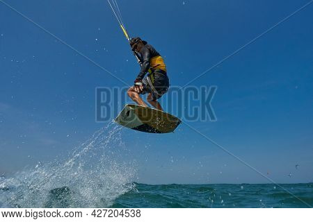Kite surfer rjumps with kiteboard  in transition and throws up the boardKite surfer rjumps with kiteboard  in transition and throws up the board