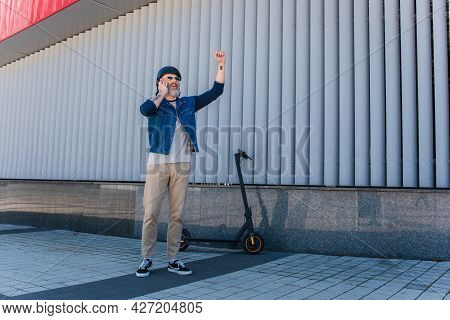 Full Length Of Happy And Mature Hipster In Helmet And Sunglasses Talking On Smartphone And Gesturing