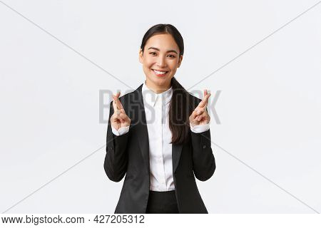 Hopeful Businesswoman Awaiting For Promising Results, Cross Fingers Good Luck And Smiling Optimistic