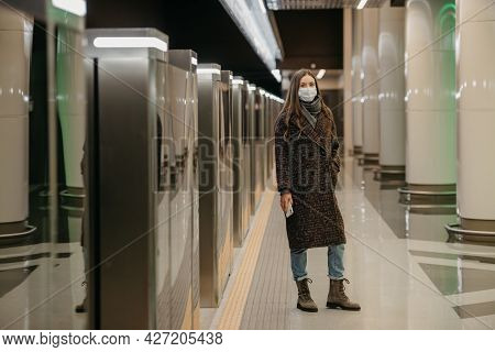 A Full-length Photo Of A Lady In A Medical Face Mask To Avoid The Spread Of Covid Is Waiting For A T