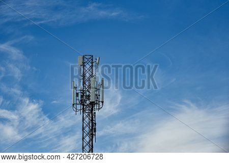 Telecommunication Towers With Motions Clouds On Blue Sky Background. Tower Signal In Blue Sky White