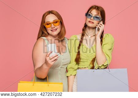 Freckled Woman In Sunglasses Talking On Smartphone Near Friend With Shopping Bag Isolated On Pink