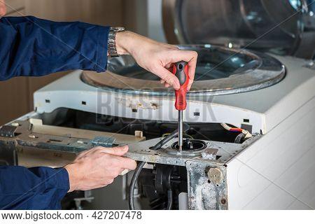 Mechanic Or Technician Is Repairing Old Washing Machine.
