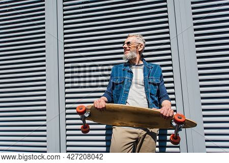 Positive And Middle Aged Man In Sunglasses Holding Longboard