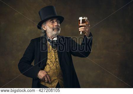 Elderly Gray-haired Man, Gentleman, Aristocrat Or Actor Drinking Beer Isolated On Dark Vintage Backg