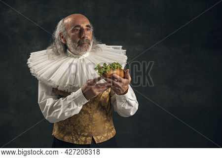 One Elderly Gray-haired Man, Medieval Hystorical Person, Actor Tasting Fast Food Isolated On Dark Vi