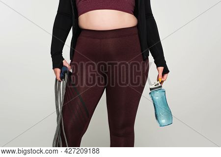 Cropped View Of Plus Size Sportswoman Holding Sports Bottle And Jump Rope Isolated On Grey