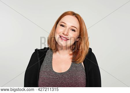 Smiling Plus Size Sportswoman Looking At Camera Isolated On Grey