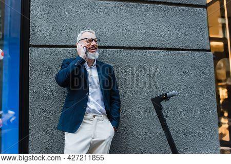 Happy Mature Businessman In Blazer Talking On Cellphone Near E-scooter