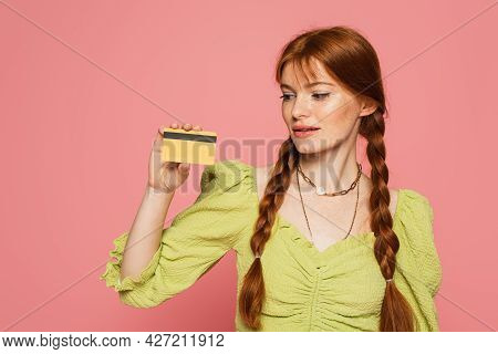 Freckled Woman Looking At Credit Card Isolated On Pink