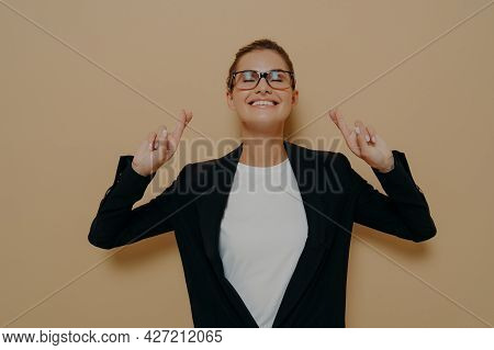Young Hopeful Woman Wearing Eyeglasses In Black Blazer Over White Tshirt Crossing Her Fingers With H