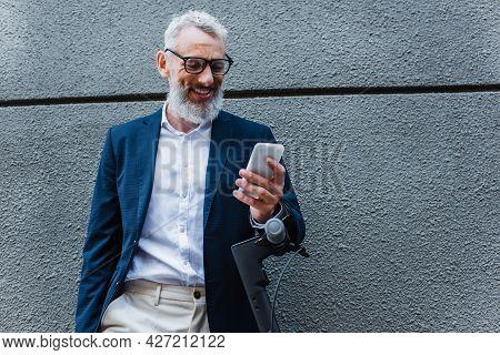 Smiling Mature Businessman In Blazer Using Smartphone Near E-scooter