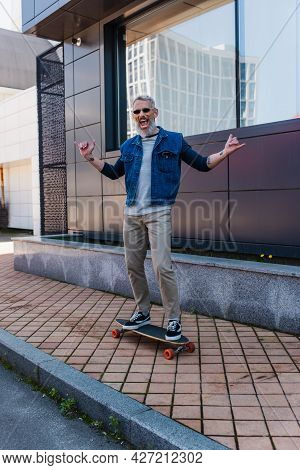 Full Length Of Excited Man With Open Mouth Riding Longboard And Showing Rock Sign On Urban Street