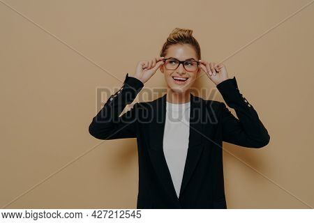 Happy Female Student In Black Blazer Over White Tshirt Adjusting Her Spectacles And Smiling Widely A
