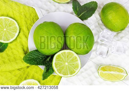 Top View Of Fresh Green Juicy Limes And Lime Slices With Mint Leaves In The Kitchen On Light Backgro
