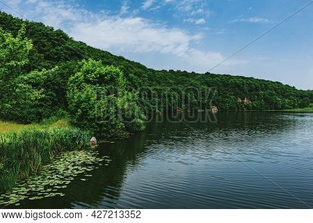 Beautiful Summer Landscape With River And Green Forest. Amazing Cloudy Sky.