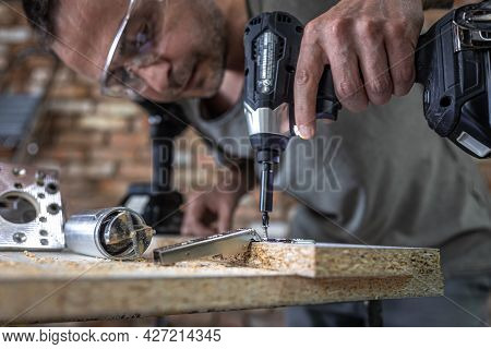 Screwing A Self-tapping Screw Into A Metal Fastening Hole On A Wood Strip Using A Screwdriver, The W
