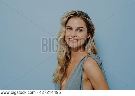 Portrait Of Cheerful Smiling Blonde Girl Dressed In Blue Dress, Standing Sideways With Toothy Smile