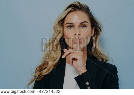 Blonde Beautiful Young Woman Wearing Black Coat Making Shush Gesture With Her Hand, Telling Someone