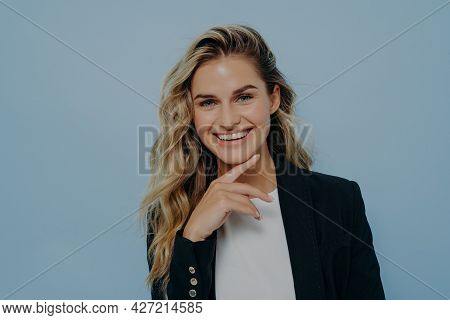 Portrait Of Young Attractive Female With Finger On Her Chin Showing Confidence With Gesture And Smil