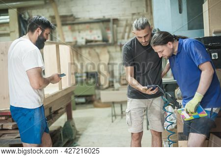 Carpenters Resting In Workshop And Scrolling On Smartphone